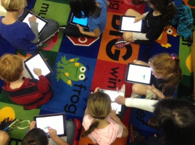 Kindergarten children using iPads in the classroom